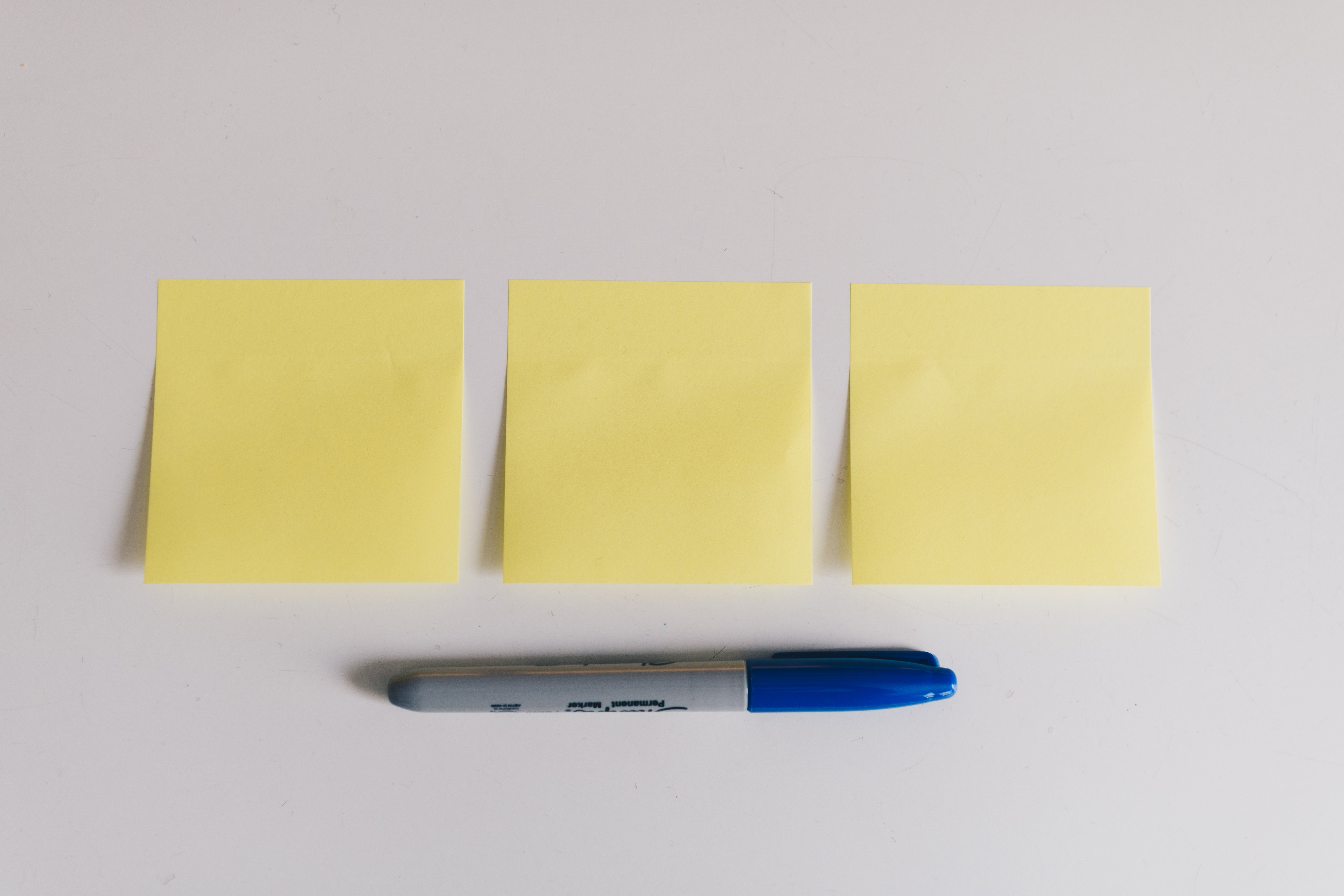 Set 3 New Years Resolutions for your Small Business (photo of 3 Post-It Notes and marker)
